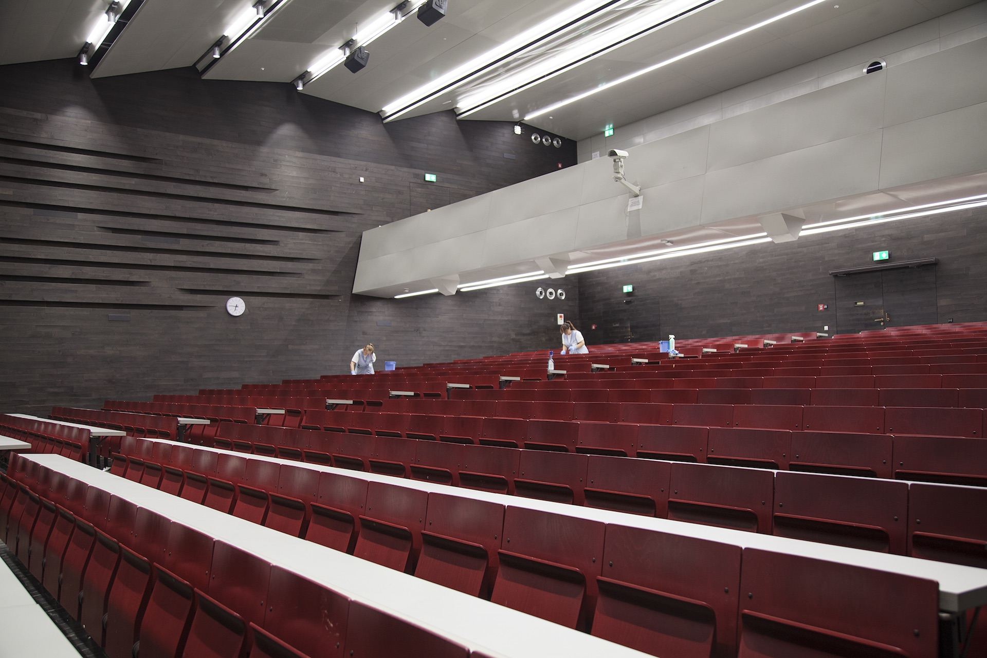 Image of an empty lecture hall at the University of Vienna and two cleaners between the seats.